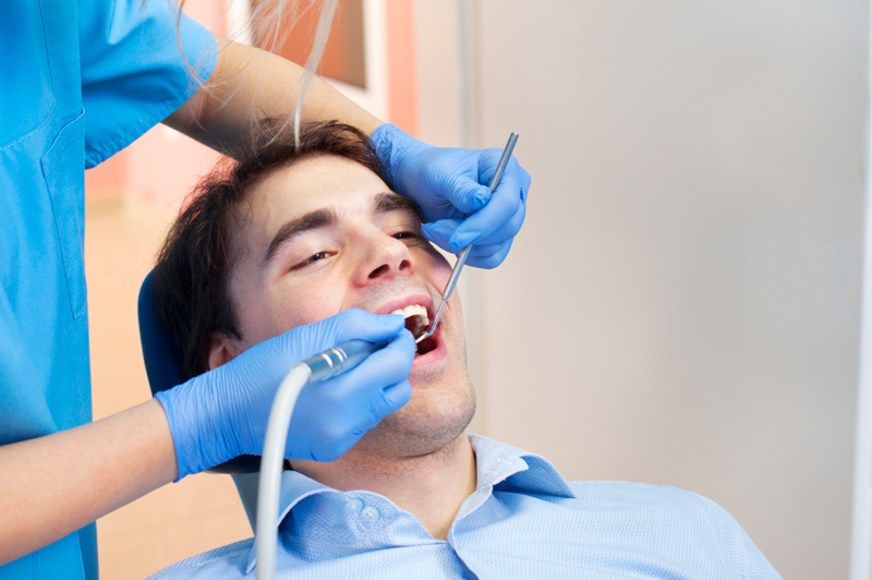 Man in dental chair getting teeth cleaned by Williston Park dentist at Long Island Smile.